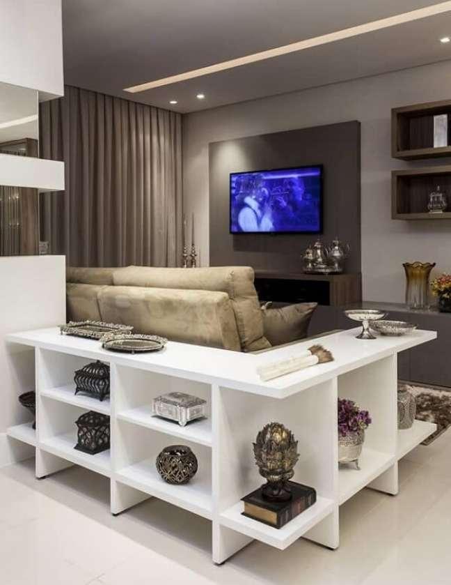 44. Neste projeto de sala planejada pequena o aparador abraça o sofá e otimiza o espaço. Projeto de Vanja Maia