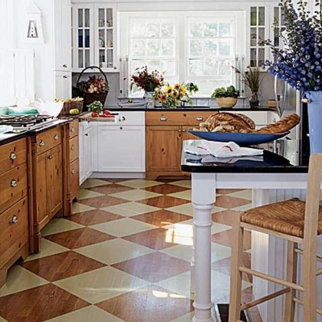 5. Decoração de cozinha com armários de madeira e piso xadrez marrom e bege – Foto: Lepsie Byvanie