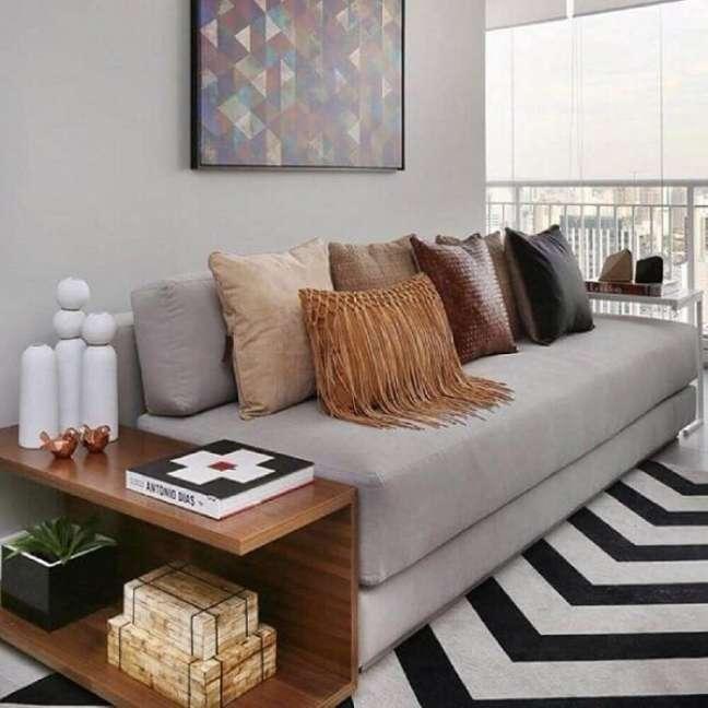 48. Na sala planejada pequena a mesa lateral pode seguir a altura do sofá. Fonte: Chris Silveira