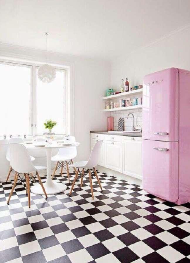 35. Piso preto e branco xadrez para cozinha branca decorada com geladeira rosa e mesa redonda – Foto: Roomed