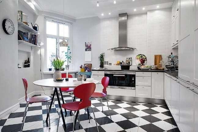 53. Piso xadrez preto e branco para decoração de cozinha com mesa redonda e cadeiras vermelhas – Foto: Jurnal de Designi Interior