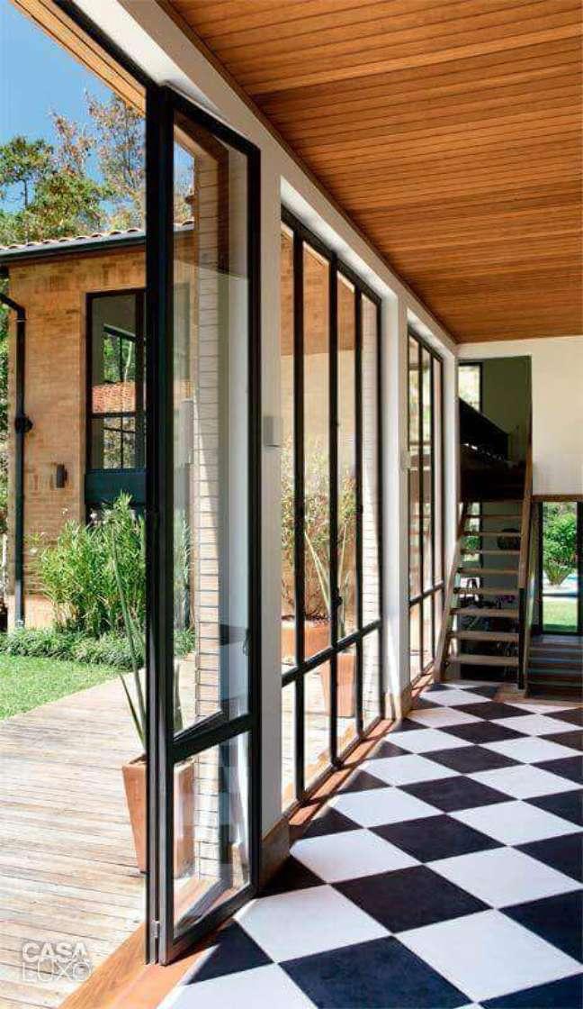 7. Piso preto e branco xadrez para decoração de casa com portas de vidro – Foto: MCA Estúdio