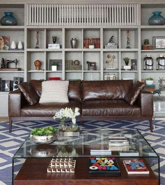 42. Tipos de sofás de couro para decoração de sala com estante de nichos e mesa de centro de vidro – Foto: Mariana Orsi Fotografia