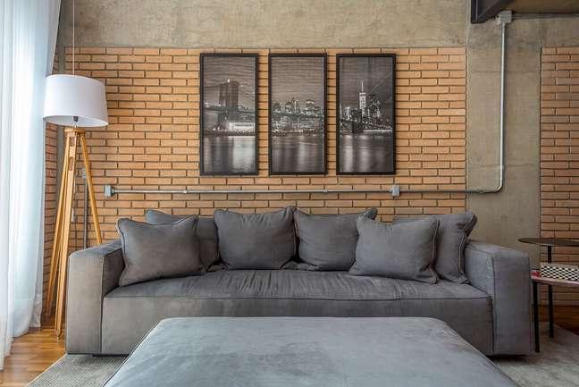 3. O sofá aconchegante se conecta com a poltrona de madeira. Foto: JP Image