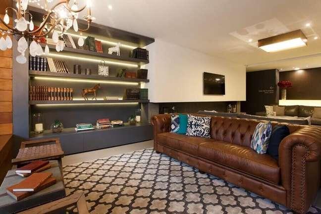 40. Tipos de sofás de couro capitonê para decoração de sala com estante cinza planejada – Foto: BG Arquitetura