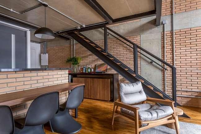 4. Embaixo da escada e próxima a poltrona de madeira um móvel é usado como aparador bar. Foto: JP Image