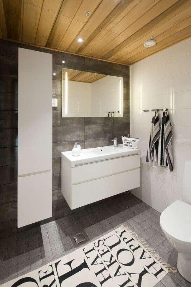 8. Banheiro cinza decorado com gabinete branco suspenso – Foto: Honka
