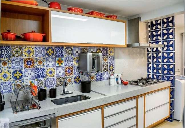 39. Gabinete branco com detalhes em madeira para cozinha decorada com cobogó azul e ladrilho hidráulico – Foto: Caio José Andrade