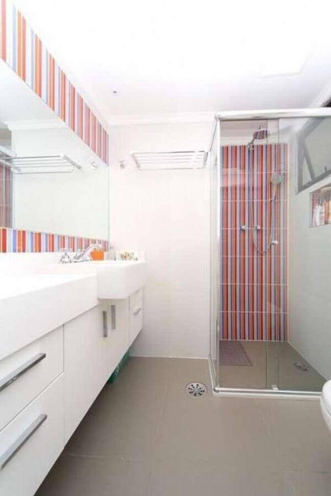 44. Gabinete branco para banheiro decorado com revestimento listrado – Foto: Olividros