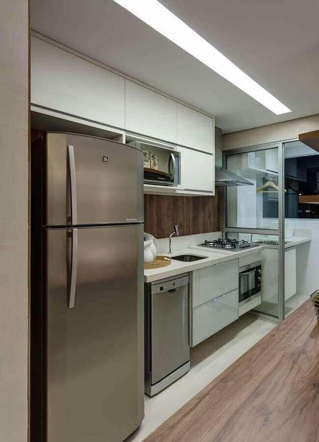 12. Cozinha de apartamento decorada com gabinete branco e armário aéreo – Foto: Renata Basques