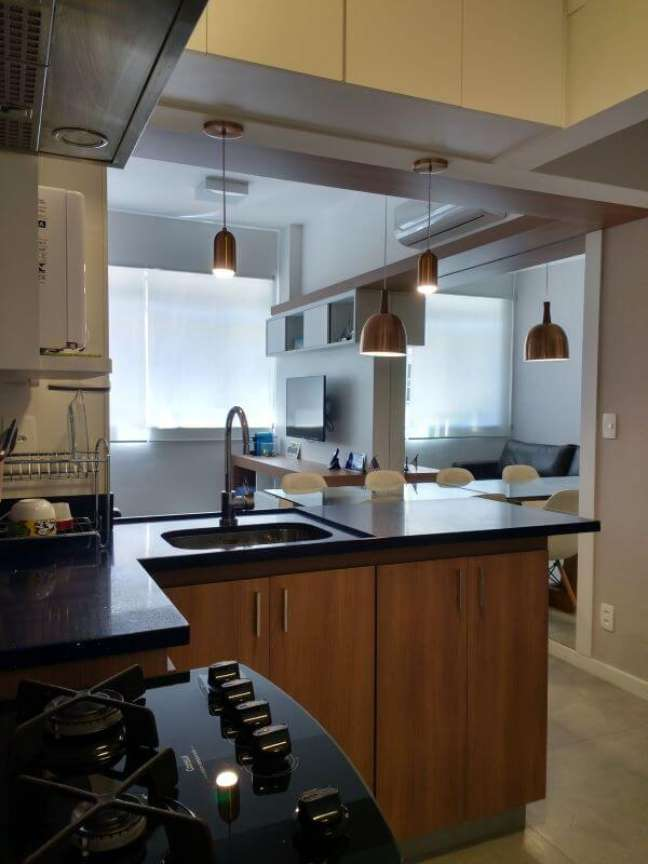 45. Cozinha integrada com a sala dividida pela bancada de quartzo preto – Foto Maria Helena Torres