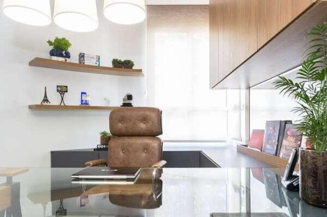 51. Escritório pequeno planejado com cadeira de couro marrom e bancada de vidro comum. Projeto de Alex Bonilha