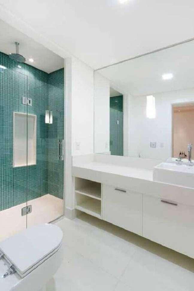 45. Gabinete branco para banheiro grande decorado com pastilhas verdes na área do box – Foto: Camila Tannous