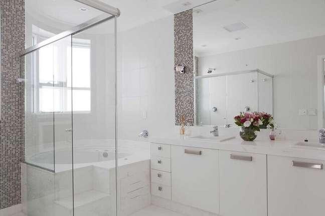 42. Gabinete branco para banheiro decorado com pastilhas e banheira de hidromassagem – Foto: Erica Salguero