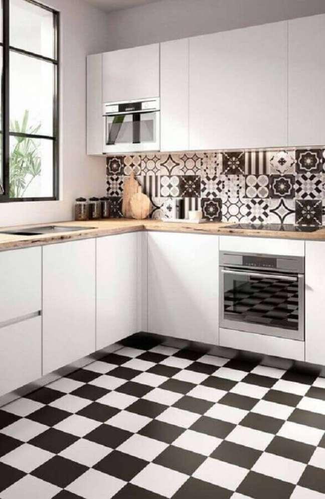 48. Gabinete branco para cozinha de canto decorada com bancada de madeira e piso xadrez – Foto: Decor Fácil