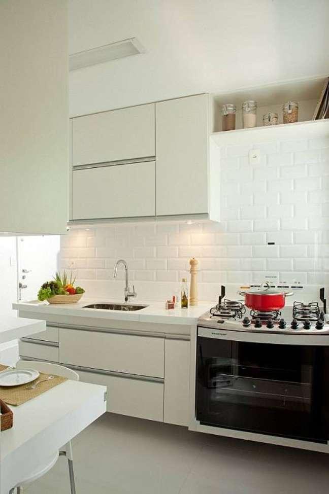 56. Gabinete de pia branco para cozinha compacta decorada com fogão de embutir – Foto: Renata Molinari