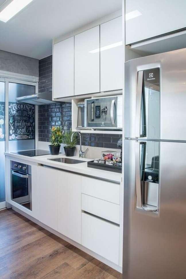 13. Cozinha pequena decorada com revestimento preto e gabinete branco – Foto: Casa Claudia