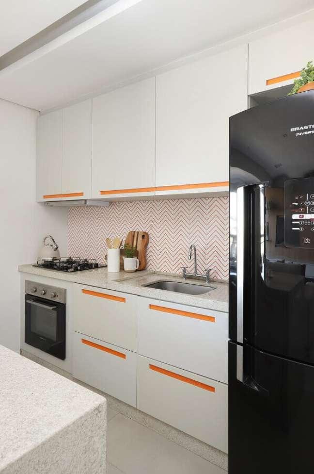 51. Gabinete branco para cozinha planejada decorada com detalhes na cor laranja – Foto: Studio Canto Arquitetura
