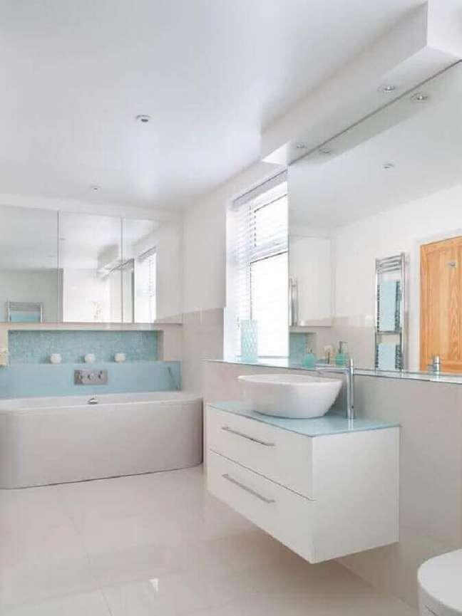 23. Decoração de banheiro azul e branco com banheira de imersão e gabinete branco pequeno – Foto: Houzz