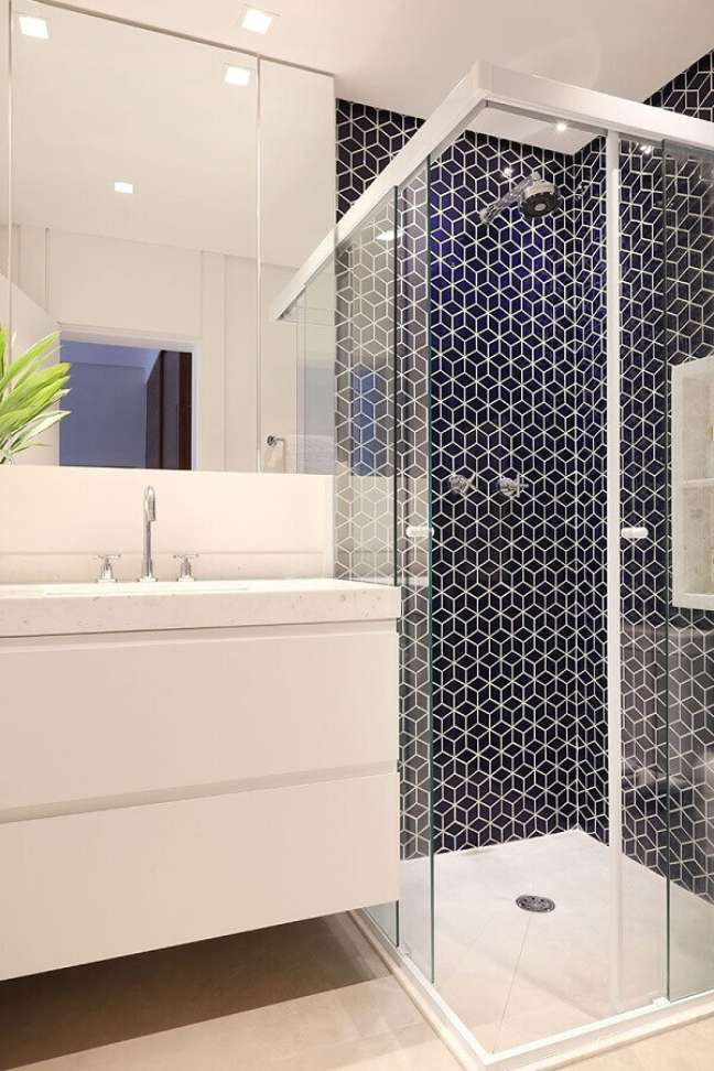 52. Gabinete branco suspenso para banheiro decorado com revestimento azul marinho – Foto: Sesso e Dalanezi Arquitetura