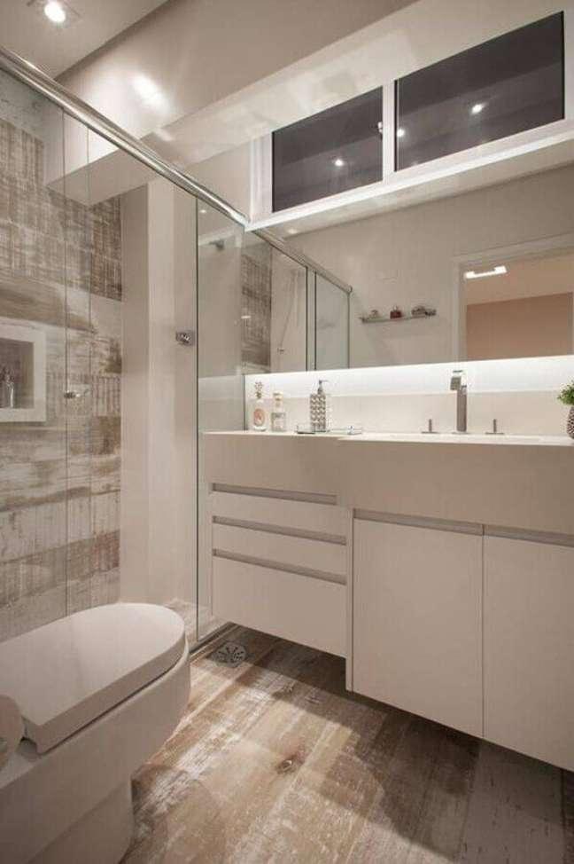 10. Banheiro pequeno decorado com gabinete branco planejado e revestimento que imita madeira – Foto: Roberta Salviatto Andreo
