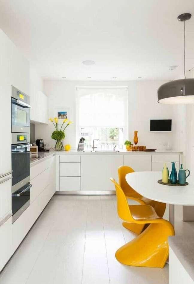 50. Gabinete branco para cozinha planejada decorada com cadeira amarela – Foto: Loft LAB