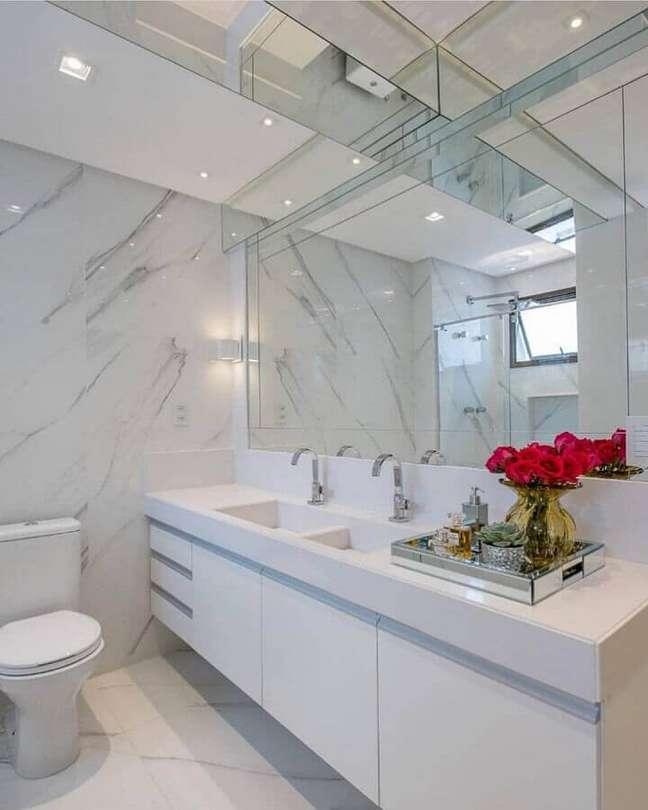 53. Gabinete branco suspenso para decoração de banheiro com bandeja espelhada – Foto: Dicas Decor