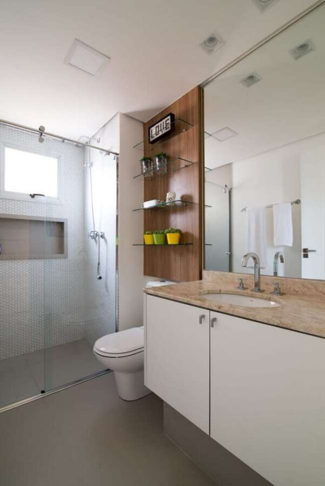 31. Decoração em cores neutras com prateleiras de vidro e gabinete branco para banheiro – Foto: Anyela Corrêa