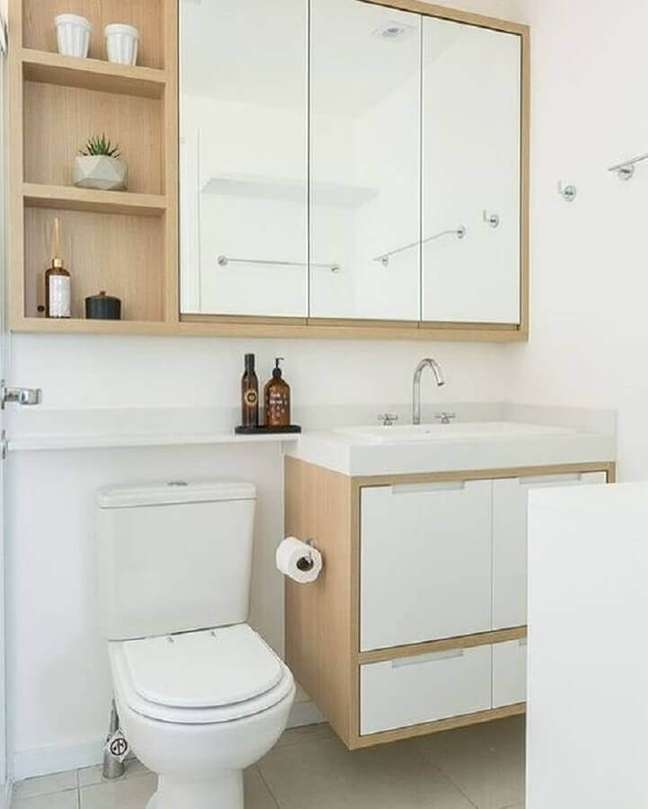 9. Banheiro pequeno decorado com espelheira e gabinete branco com detalhe em madeira – Foto: Arkpad