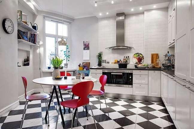 49. Gabinete branco para cozinha de canto decorada com cadeiras vermelhas e piso xadrez – Foto: Jurnal de Design Interior