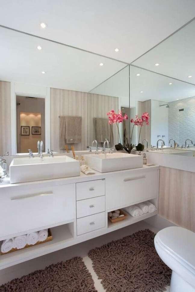 47. Gabinete branco para banheiro planejado decorado com parede espelhada e duas cubas – Foto: Apartamento Idylle