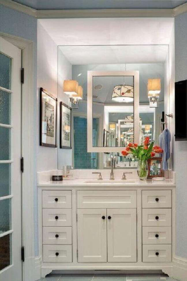 5. Gabinete branco antigo para decoração de banheiro planejado com arandela de espelho – Foto: David Scott Parker