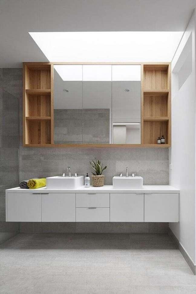 54. Gabinete branco suspenso para decoração de banheiro com espelheira de madeira – Foto: Glow Building Design