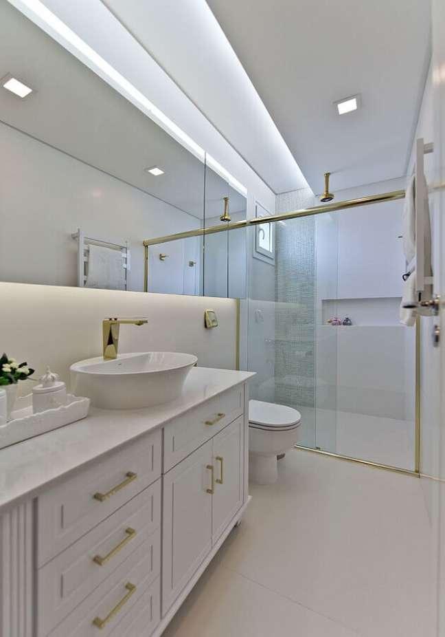 35. Decoração sofisticada para banheiro com gabinete branco e detalhes dourados – Foto: Espaço do Traço Arquitetura