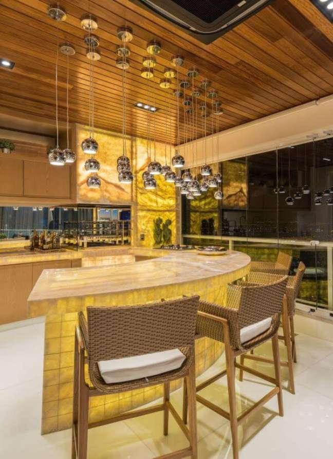 33. Decoração moderna com churrasqueira de parede e luminárias na bancada – Foto Iara Kilaris