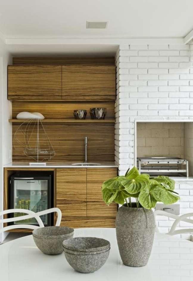 24. Churrasqueira pequena revestida com tijolinho branco moderno e gabinete planejado de madeira – Foto Diego Revollo