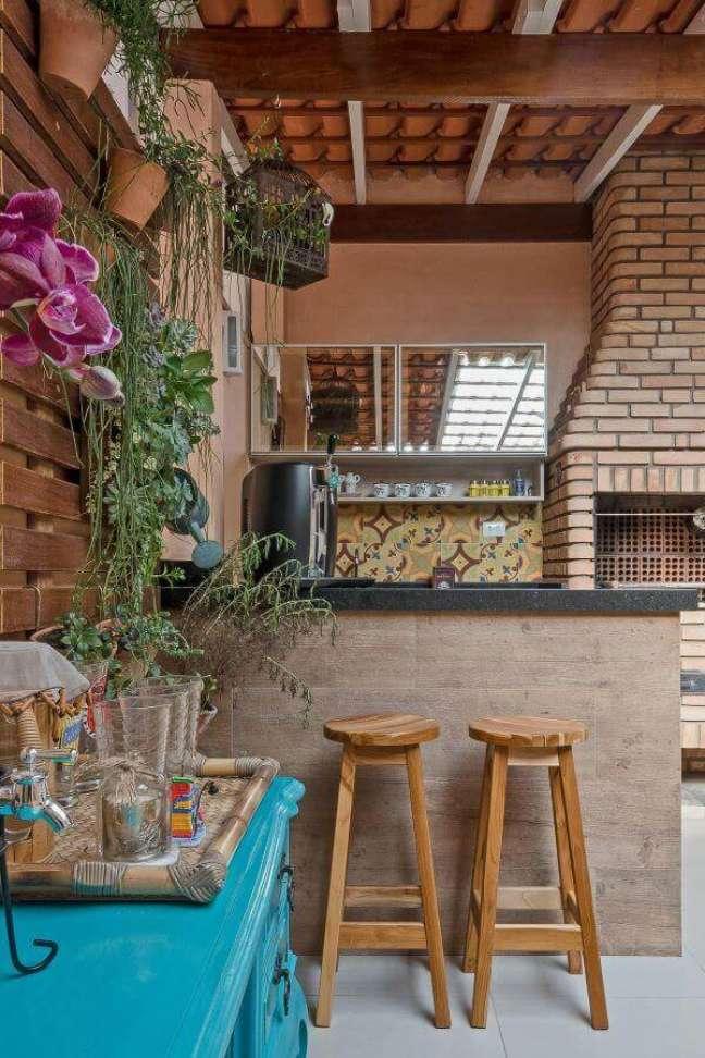 67. Área gourmet com churrasqueira pequena de tijolinho e jardim vertical perto da mesa azul – Foto Kathia Pimmenta