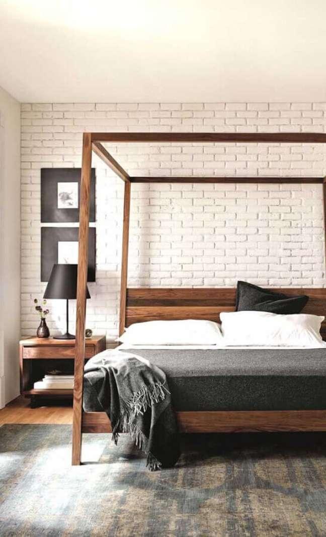 19. Cama com dossel de madeira para quarto de casal decorado com parede tijolinho branco – Foto: DecoRecent
