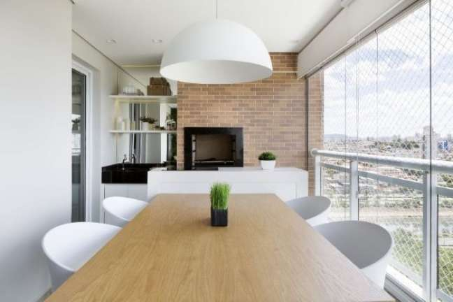 46. Varanda com churrasqueira pequena e mesa de madeira – Foto GF Projetos