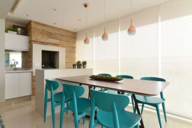 55. Varanda gourmet com churrasqueira pequena revestida com porcelanato claro e mesa de madeira com cadeiras azuis modernas – Foto Danyela Correa