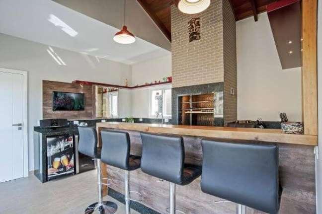 19. Churrasqueira pequena na área de lazer moderna com balcão de madeira e banquetas preta – Foto Patricia Azoni
