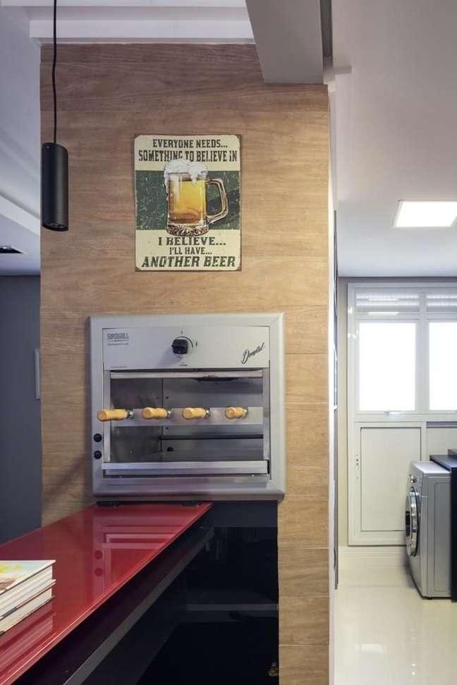 29. Cozinha com churrasqueira embutida perto da bancada vermelha – Foto Braccini e Lima Arquitetura