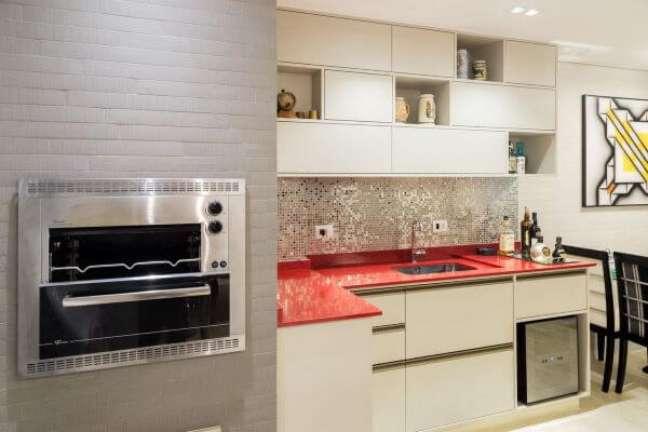 65. Área gourmet com churrasqueira pequena e cozinha com bancada vermelha moderna Foto Andrea Petini