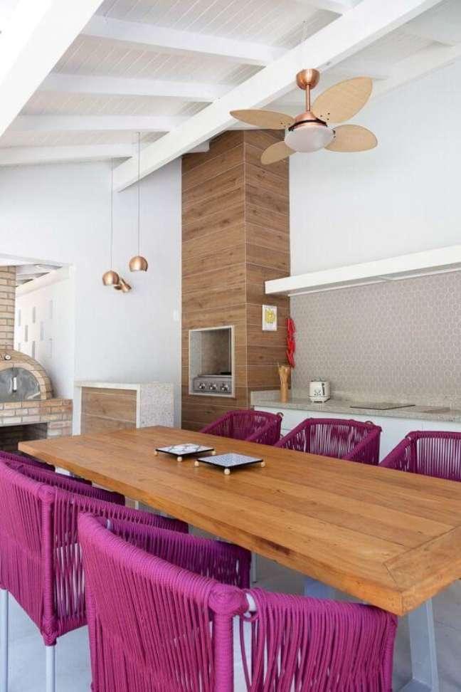 4. Área de lazer moderna com mesa de madeira e cadeiras cor de rosa e churrasqueira pequena no canto – Foto Agata Cunha