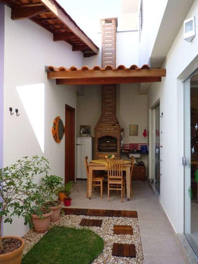 3. Quintal pequeno com espaço para churrasqueira pequena de tijolo e mesa de madeira com 4 lugares – Foto Grupo Joih