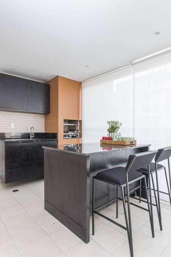 68. Área gourmet com churrasqueira pequena de tijolinho e bancada preta de granito – Foto Spaze Arquitetura e Interiores