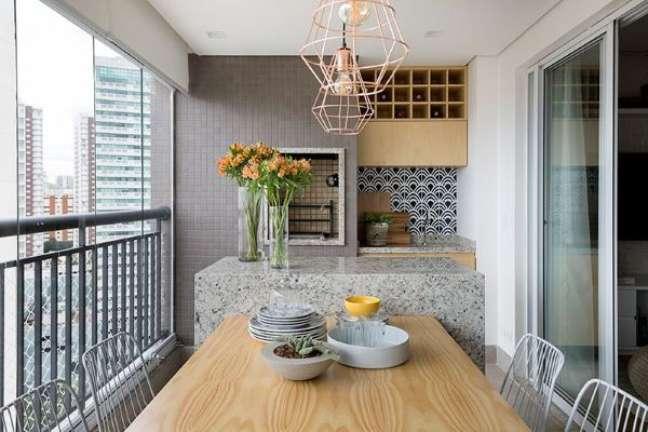 15. Churrasqueira pequena embutida na varanda gourmet com balcão de granito cinza e mesa de madeira na decoração – Foto Doob Arquitetura