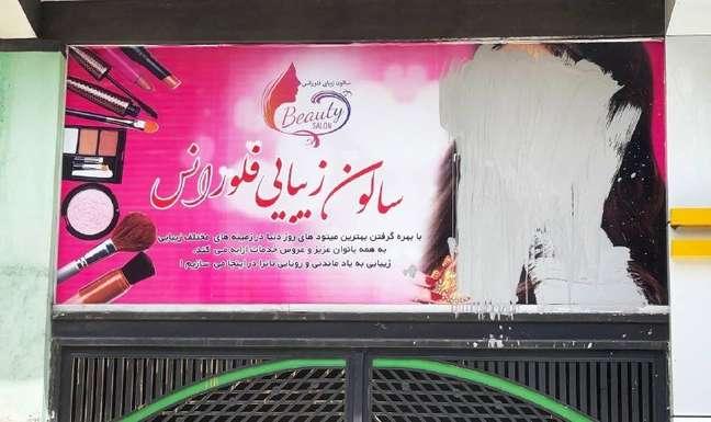 Um cartaz no Afeganistão em que o rosto de uma mulher foi riscado