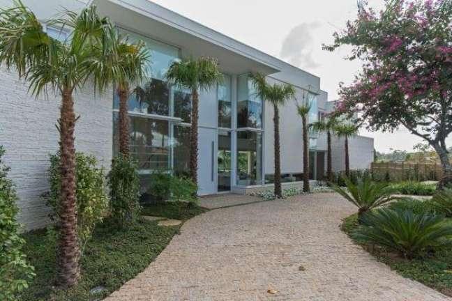 41. Fachada de vidro com revestimento de pedra canjiquinha e jardim – Foto Jannini Sagarra Arquitetura