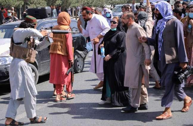 Um membro das forças do Talibã aponta sua arma para os manifestantes